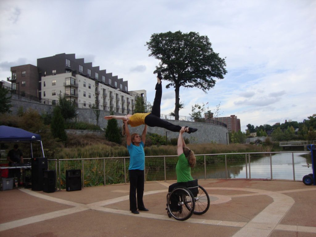 Two dancers, one in a wheel chair, hold up another dancer