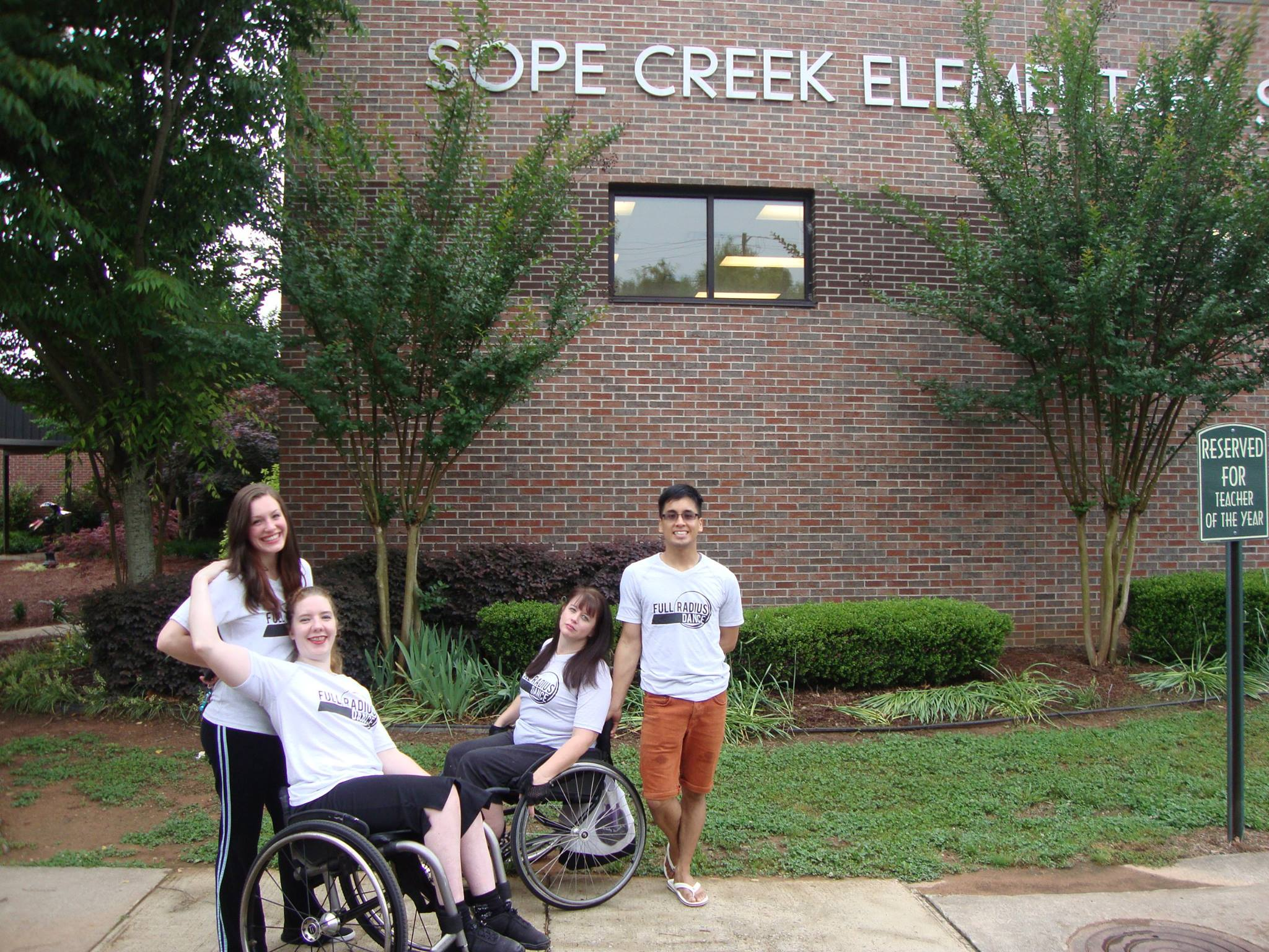 Four dancers, two in wheel chairs, pose outside of Sope Creek Elementary School
