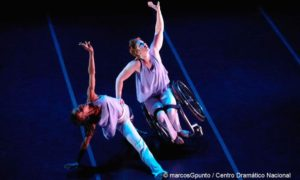 Two women reaching up passionately dancing while one women is in a wheelchair