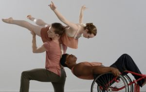 First girl kneeling down holding second girl in the air while a man, in a wheelchair, is leaning on the first girl