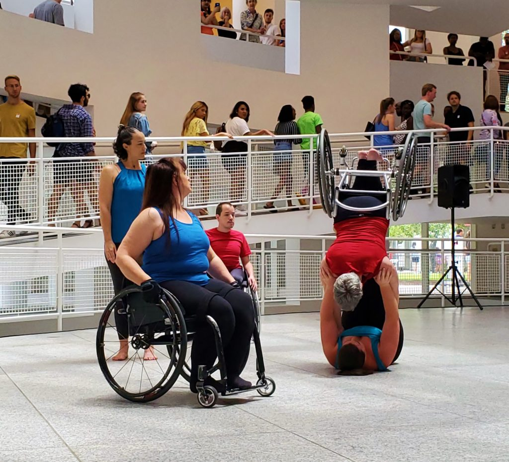 Dancer laying on her back lifts up another dancer in a wheel chair while spectators watch