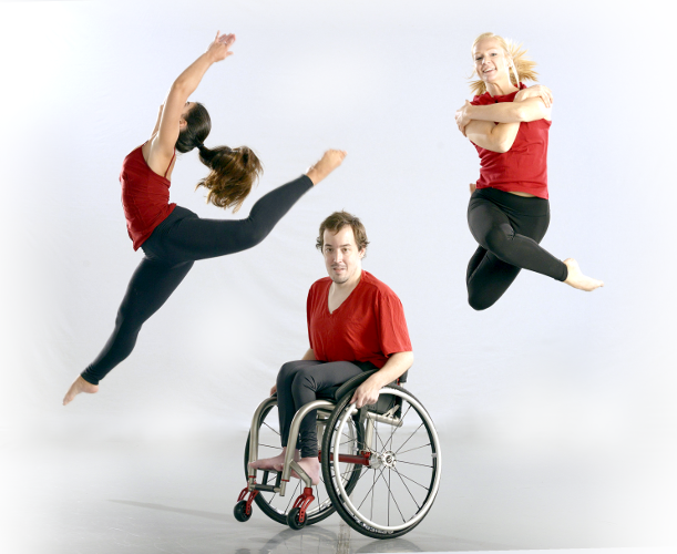 Two girls happily jumping in the air while one man in a wheelchair stays on ground