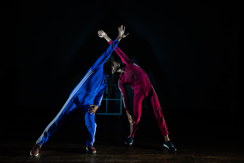 Two people, one in blue and one in red, posing
