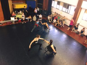 A class of dancers learn to dance with people in wheelchairs