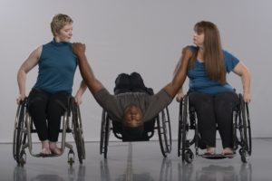 Two wheel chair dancers hold up another dancer who's leaning back