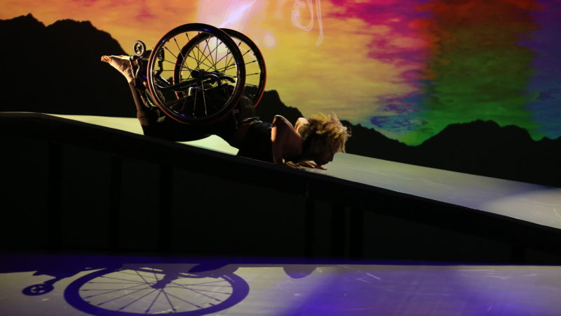 Dancer in wheel chair lays on stomach