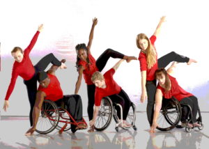 Dancers in wheel chairs and red uniforms dance with other dancers in unison