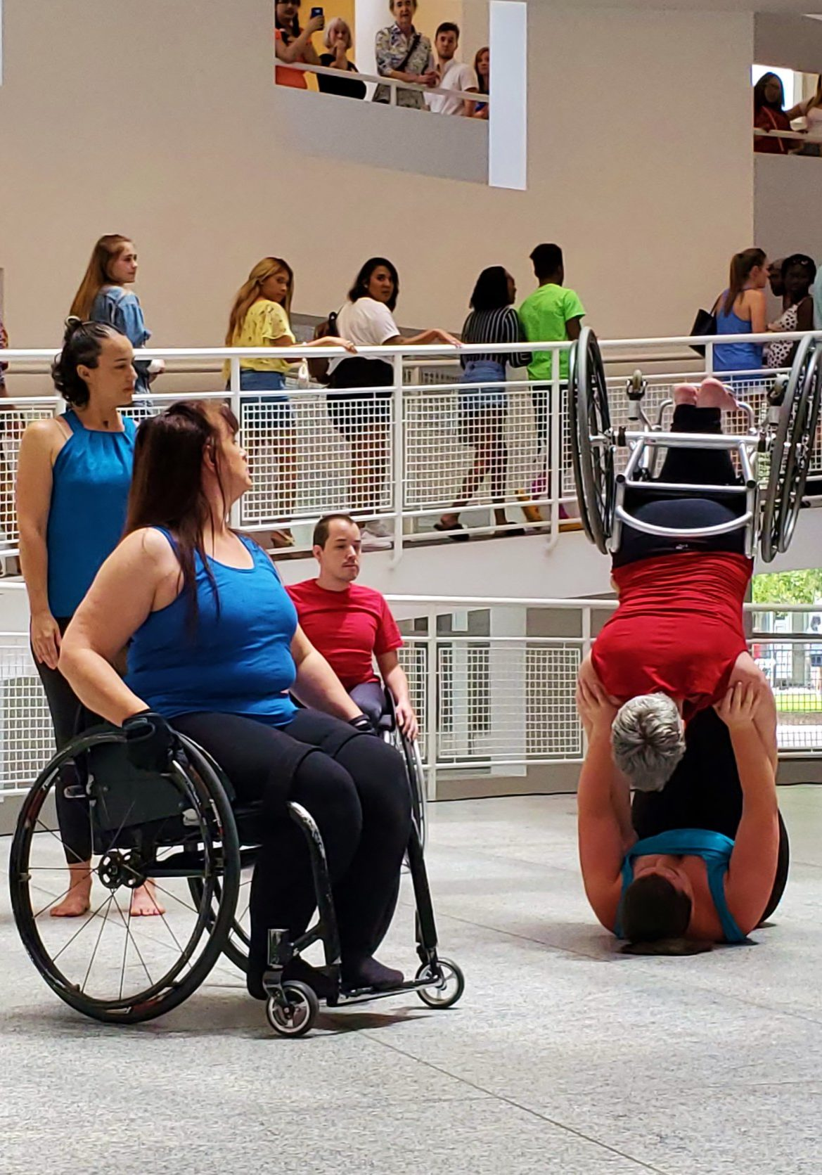 One person on wheelchair watching two other people dancing with wheelchairs